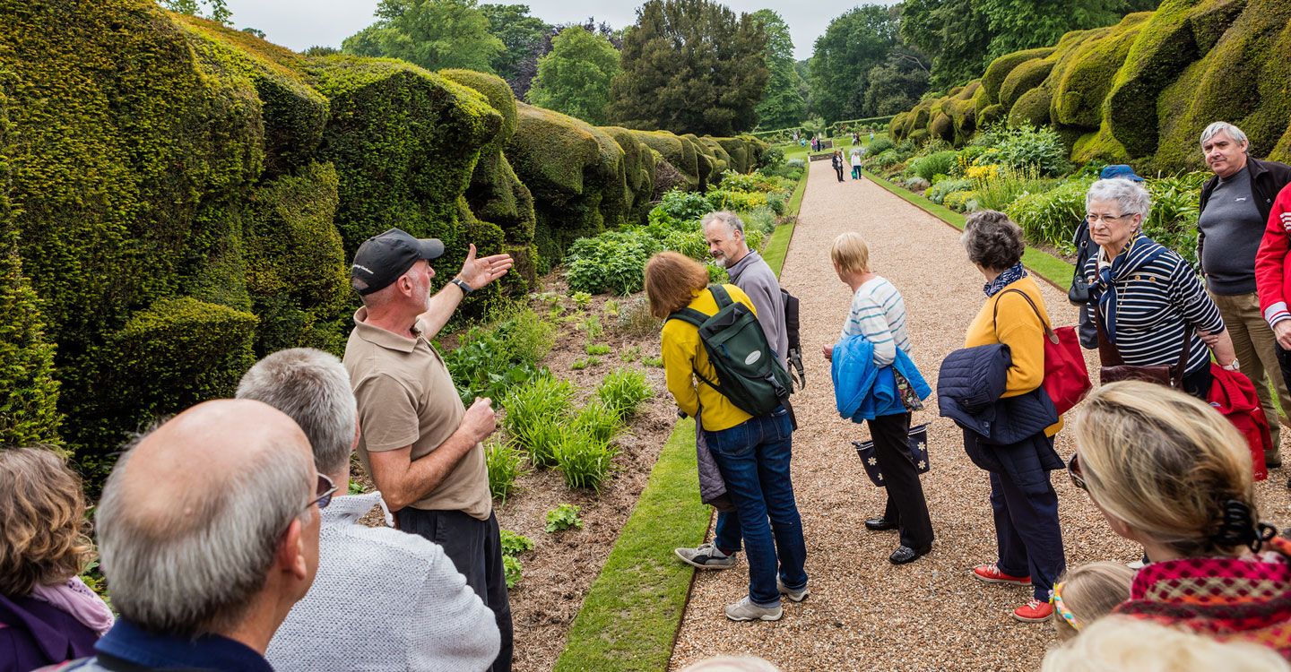 A gardener leading a group of visitors on a tour