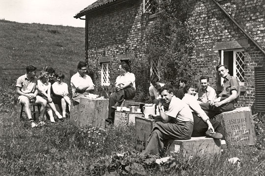 The historian Maurice Beresford, the archaeologist John Hurst, students, and the resident Milner family outside Wharram Percy Cottages in the 1950s