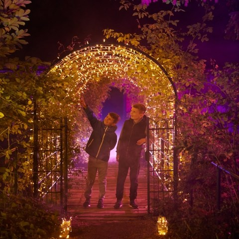 Two children under a lit up archway at Enchanted Audley.