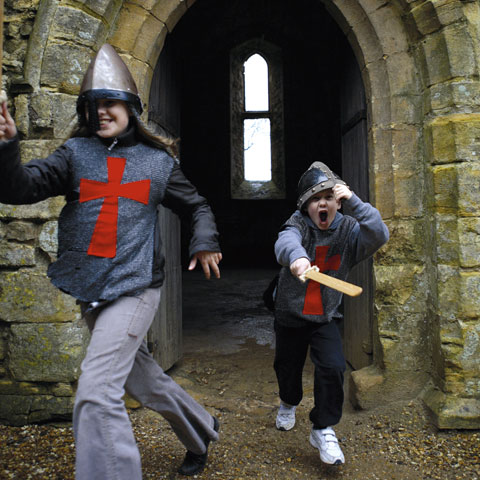 Children dressed as Norman knights play in the ruins of Battle Abbey.