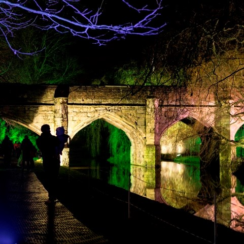 The silhouette of an adult and child infront of the moat at Eltham Palace, lit up for Enchanted Eltham.