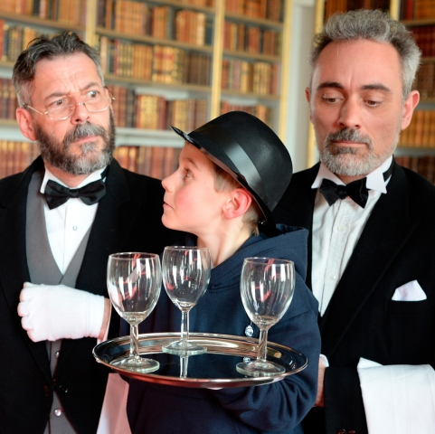 Two butlers teaching a young aspiring butler the ettiquette required in an English country house.