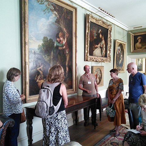 Kenwood volunteer talking to a group about a painting in the house.
