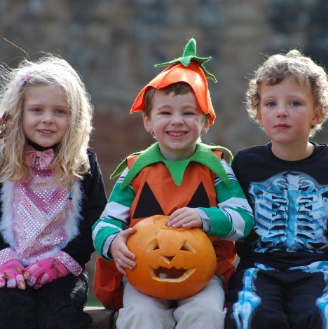 Three children dressed up as a cat, pumpkin and skeleton.