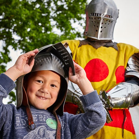 A child tries on armour with a knight