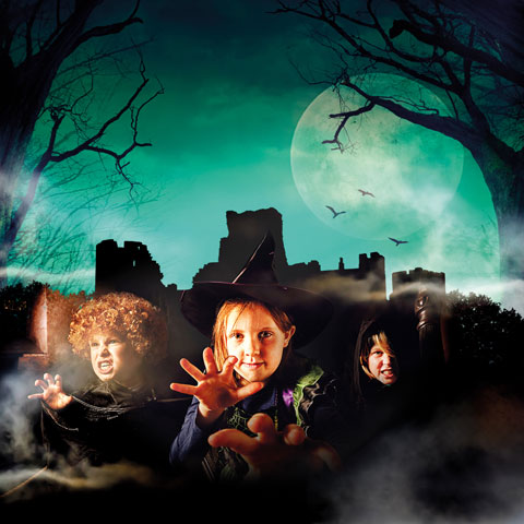 Children in Halloween costume in front of a spooky castle.